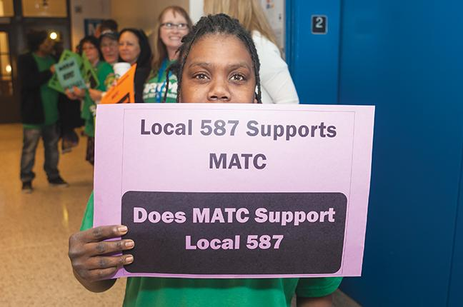 Rachel Spencer  holds her Local 587 support sign, with more supporters behind her.