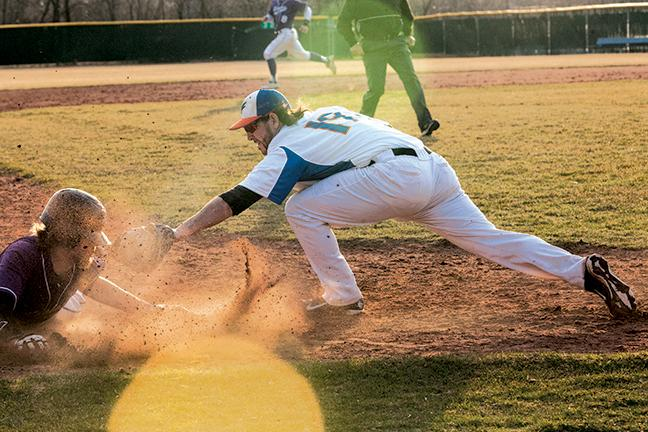 Jacob Hornik (19) tries to tag out Buddy Ahlstrom (19) an Illinois Valley Community College Eagle, during a double header.