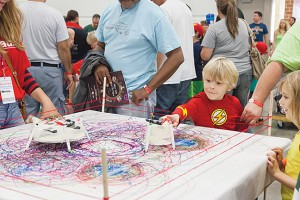 A child is mesmerized by the drawing machine at the Maker Faire.