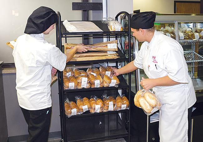 Tabitha+Komoski+and+Crystal+Miller%2C+Baking+and+Pastry+program+students%2C+put+out+bread+items+for+students+to+purchase+throughout+the+day.+