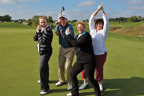 Michelle Krueger, Daniel McColgan, Jody Burdick and Kathleen Hohl celebrate halfway through the golf tournament with their version of Charlie's Angels – Dan's Angels.