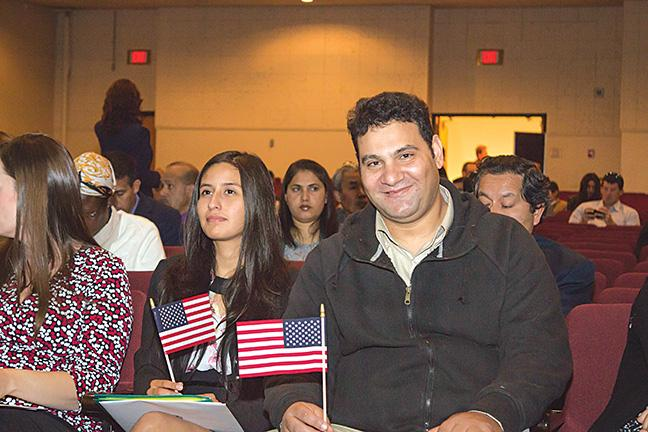 Meribeth Mazzi (L) from Peru and a smiling Ibrahim Saad (R) from Egypt hold their flags. They both waited 10 years to be naturalized citizens.