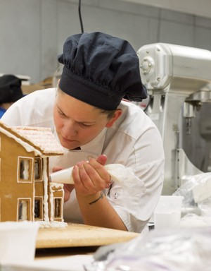 Lauretta Archibald, Baking and Pastry Arts program, pipes icing onto her gingerbread house for the annual gingerbread house competition.