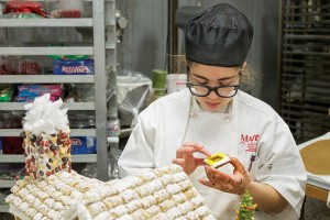 Rebecca Frazier, Baking and Pastry Arts program, attaches colored gelatin to a ginger cookie frame to make the windows for her and Octavia Lewis' gingerbread house for the competition.