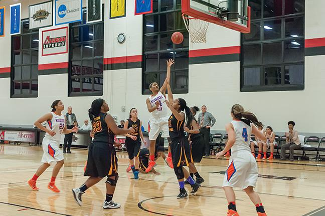 One of two returning players, Briana McKinney (#14) goes for a lay up against the Trojans.