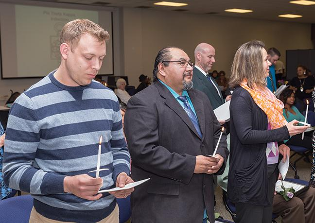 From left, Joseph Coraggio, Jose DeHoyos and Darija Krecak hold candles during the PTK Honors Induction Ceremony.