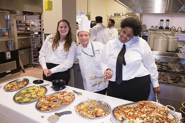 Nikie Brand (L), instructor Chuck Stepanovich, and Sabrina Coleman (R) hand out specialty pizzas such as pesto and lobster, spicy chorizo and portobello mushrooms with prosciutto.