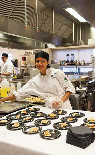 Culinary Arts program student Heena Dhyani prepares the finishing touches on several dishes.