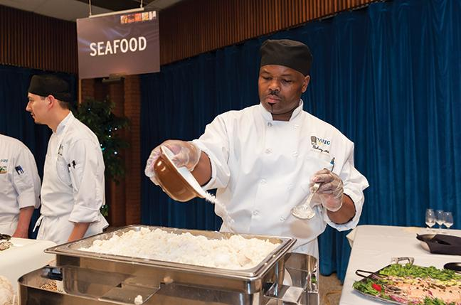 Gary Morse, Culinary Arts program student, works at the seafood area at the Five Star Food and Wine Evening on April 23.