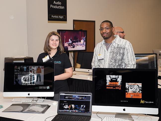 Odeliz Rodriguez and Keenen Edwards both Graphic Design students showing off their work.