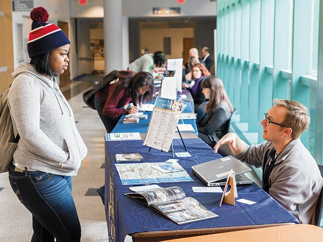 Destiny McClendon (L) of the Dental Hygiene program gets information from Adam Stout, assistant dean transfer coordinator for Marquette University during Transfer Days at the Downtown Milwaukee campus on Oct. 13.