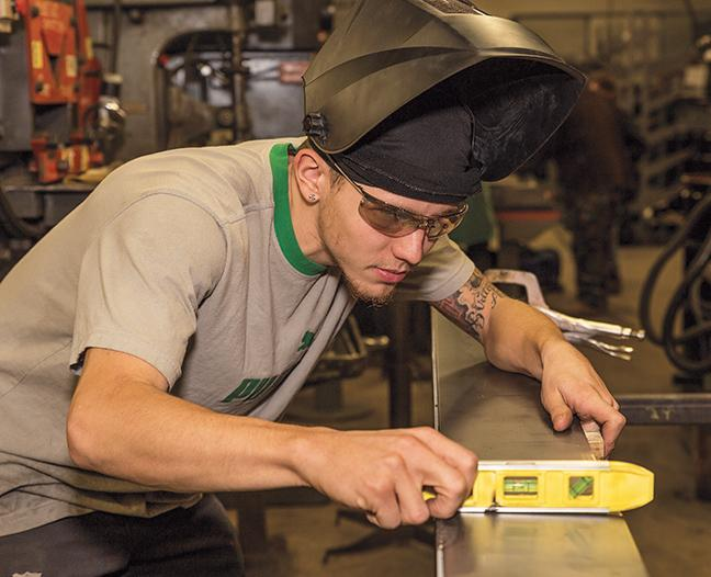 Checking the level of the frame for the South Milwaukee High School project is Devin Schroeder, of the MATC Welding program, at the welding shop on the Oak Creek campus.