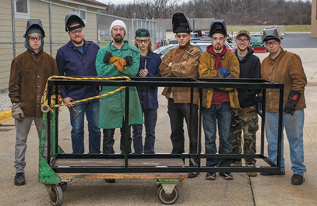 The welding student participants stand behind their first completed frame for the Robotics Club of South Milwaukee High School.