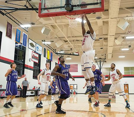 """Thomas """"Tommie T"""" Hood (12) lays the ball in the basket as the Wolves watch."""