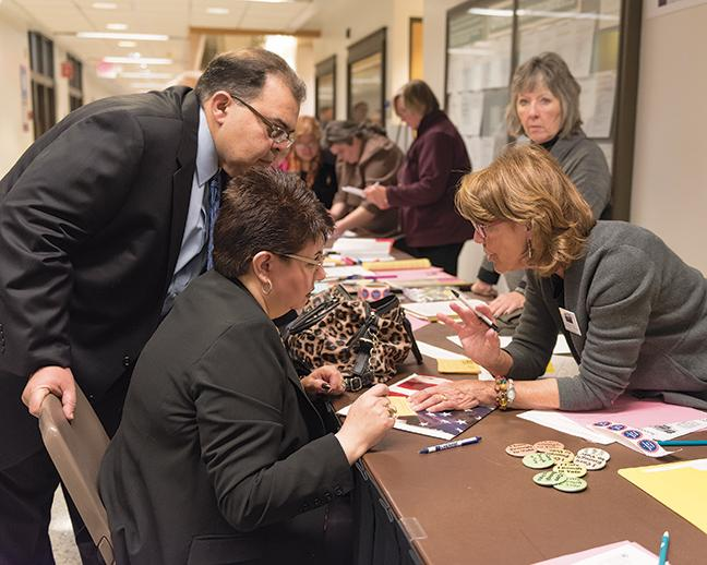 JoAnn Walsh helps new US citizens, Moe Hammad and Ingrid Hammad, register to vote.
