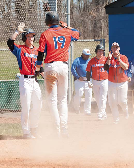 Eric Pascutti (10) congratulates teammate, Fred Brower (19) after Bower scored the winning run against the Wolves in the first game of a doubleheader.
