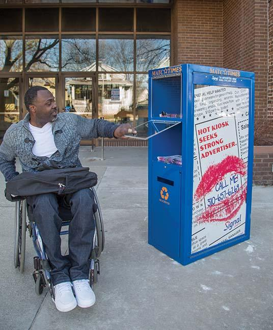 Bernard Funches, a Liberal Arts program student, reaches into one of two new newsstand kiosks at the West Allis Campus.