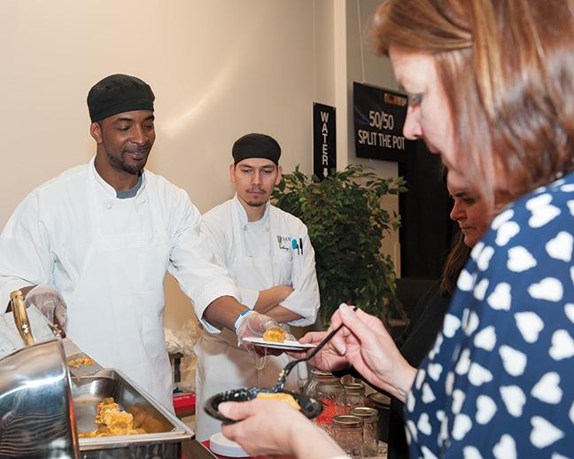 Greg Story, Culinary Arts program, watches as Jeff Matthews, Culinary Arts program, hands out food at the brisket station.