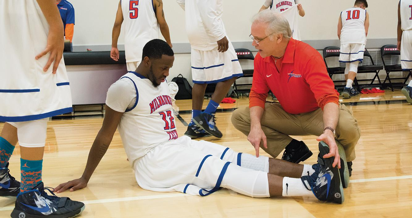 John Larson, right, examines Thomas Hood Jr. after he sustained an injury.