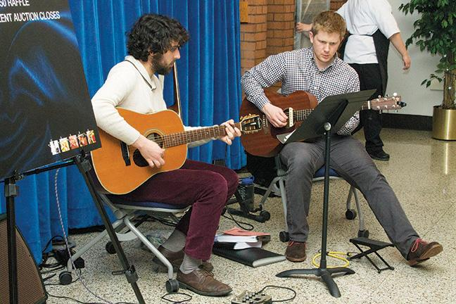 Music Occupations program students Andrew Koenig (R) and Eric Fricke entertain guests with acoustic music during the Five Star fundraiser event.