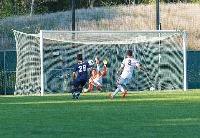 Goal keeper Francisco Campechano (1) tries to block the shot on goal by Angel Sarti (26) of Harper College.