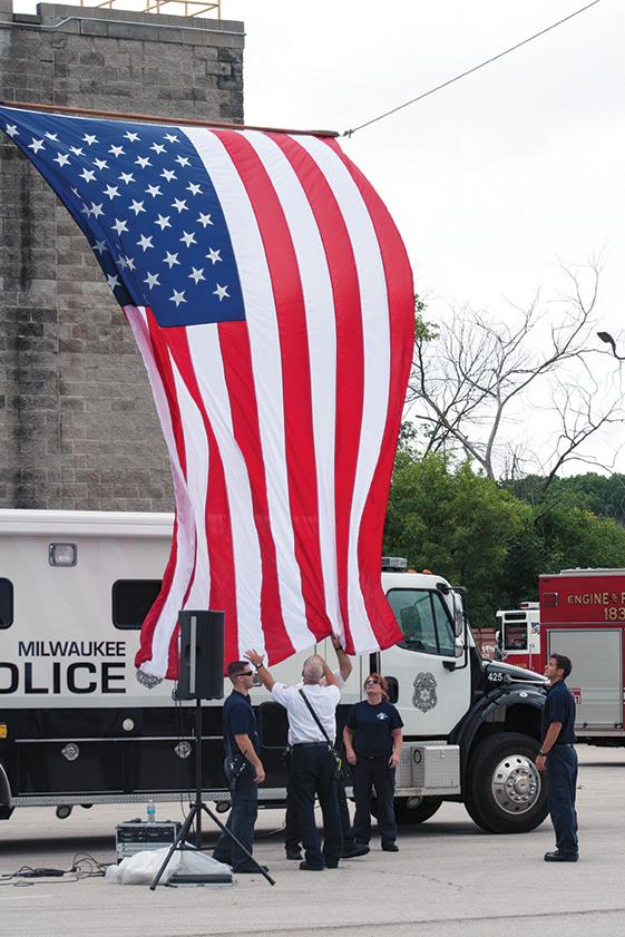Police and firefighters set up American flag in preparation for 9/11 commemoration ceremony.