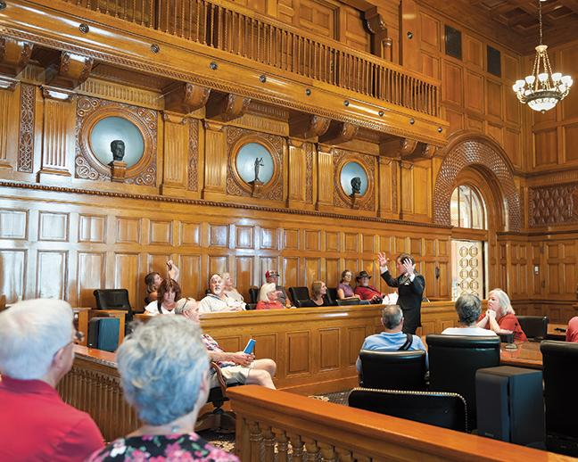 A lawyer explains the history of the Ceremonial Courtroom, which includes metal busts chosen by a former judge at the Federal Courthouse.