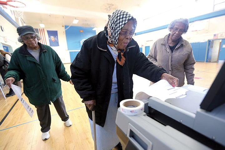 Ellen Williamson, center, feeds her ballot as friends Erma Carter, left, and Earnestine Roberson stand by as people cast their votes at Parkway Elementary School in Glendale, Wis., on Tuesday, April 5, 2016. (Mike De Sisti/Milwaukee Journal Sentinel/TNS)