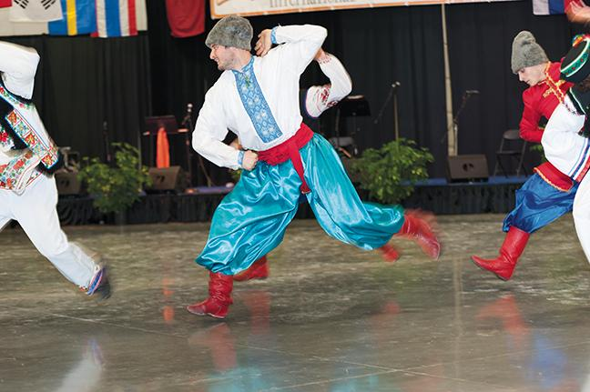 A male member of the Ukranian dance group performs a jump as part of the dance.