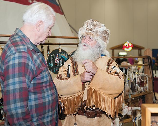 Turtle Joe Wacker, 1840's reenactor, fur trade, cowboy, and miner, explains to Jim Kusik, West Allis, about his experience as a reenactor.