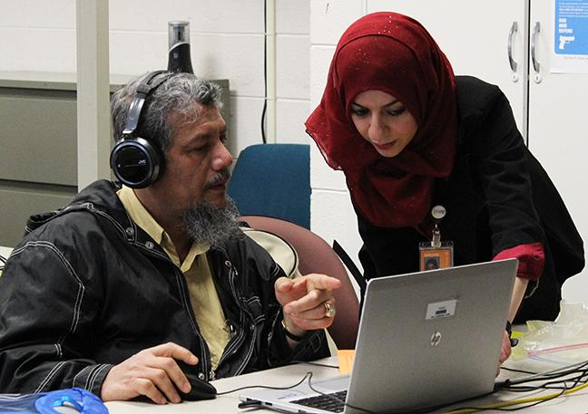 Bara Omari helps an ESL student with his work at the MATC Downtown campus.