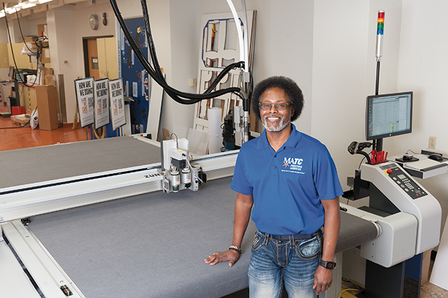 Gerald Trotter, Manager of Printing Services, poses in front of the newest equpiment acquired by printing services, the Zund Cutter.