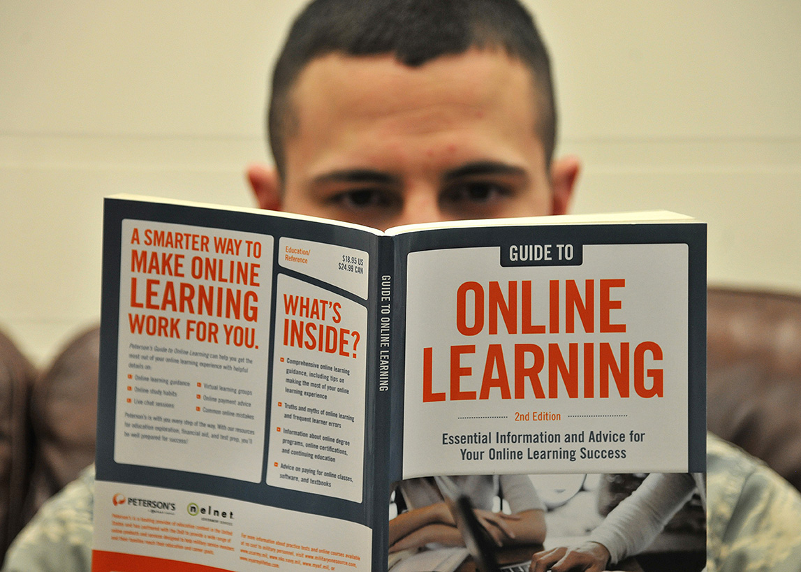 Senior Airman Kyle Struecker, 69th Maintenance Squadron crew chief, reads a book on online learning  at the Education Center on Grand Forks Air Force Base, N.D., March 31, 2015. Stuecker has taken two college level examination program exams and has two more classes left before starting his clincals to receive an associate's degree in applied science radiologic technology. (U.S. Air Force photo by Senior Airman Xavier Navarro/released)