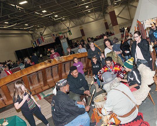 Native Americans and guests join in a drum circle at the Holiday Folk Fair International.