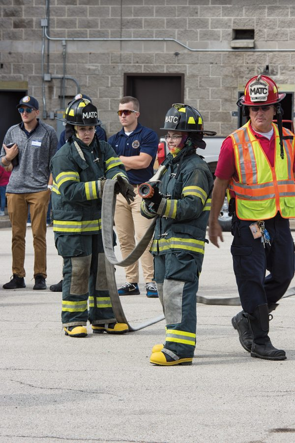 Students demonstrate proper use of firefighting equipment.
