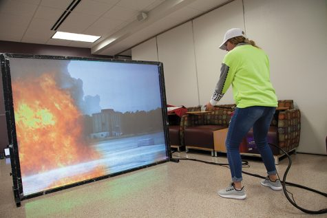 "Steffanie Peterson, first-year nursing student, ""fights"" the virtual fire and successfully extinguishes it at the Mequon campus Safety Fair."