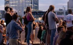 Attendees watch a performance at the US Cellular Connection Stage. As day turns into night at Summerfest, the skyline comes alive with the soft glow of stage lighting beneath the Milwaukee skyline.